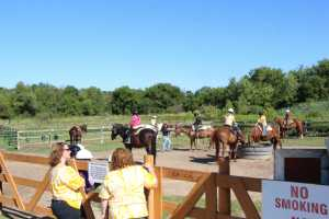 Two mothers oversee the Girl Scouts troop prepare to ride horses for the day.