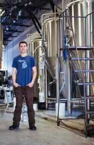 Head Brewer of Liberty Street Brewing Company, Andy Hengesh, stands next to the machines he operates everyday to make high quality beer in Livonia, Michigan.