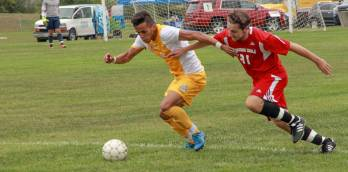 PHOTO BY ALEX REGISH | STAFF PHOTOGRAPHER Lake Michigan defender Jon Baldwin chases down Schoolcraft's forward Victor Contreras during the first half.