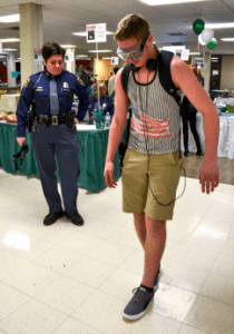 Cole Westwood tries to walk in a straight line wearing drunk goggles at the mocktail party, last March.