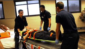 EMT students imitate transporting a victim from a car wreck.