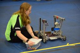 A student from Michigan Tech fixes a small robot.