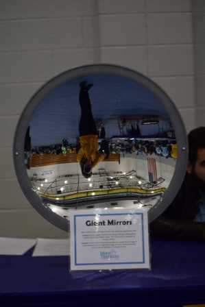 The large mirror displays how light can be bent to make different images appear.