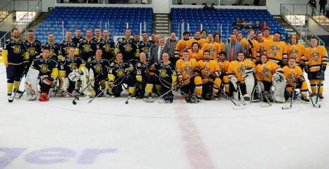 Members of the Schoolcraft College and Michigan State Troopers (MSP) Hockey teams gather at center ice for a group photo at the conclusion of the game. The MSP Troopers beat the Ocleots 8-3.
