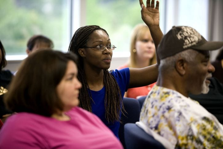 raising-her-hand-in-order-to-pose-a-question-this-african-american-woman-was-one-of-a-number-of-attendees-725x483
