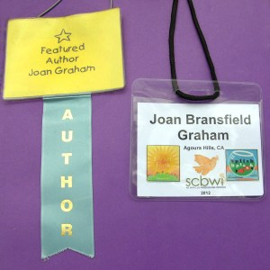 """I have a drawer full of nametags from various events, and I recycle them as needed. I use the one pictured on the left if I'm not given a nametag and need one. The one on the right is from an SCBWI conference. I print small pictures of my book covers and add them with a loop of tape on the back; then I can take them off and put them wherever I want. Including that visual helps people connect a face with a book."""