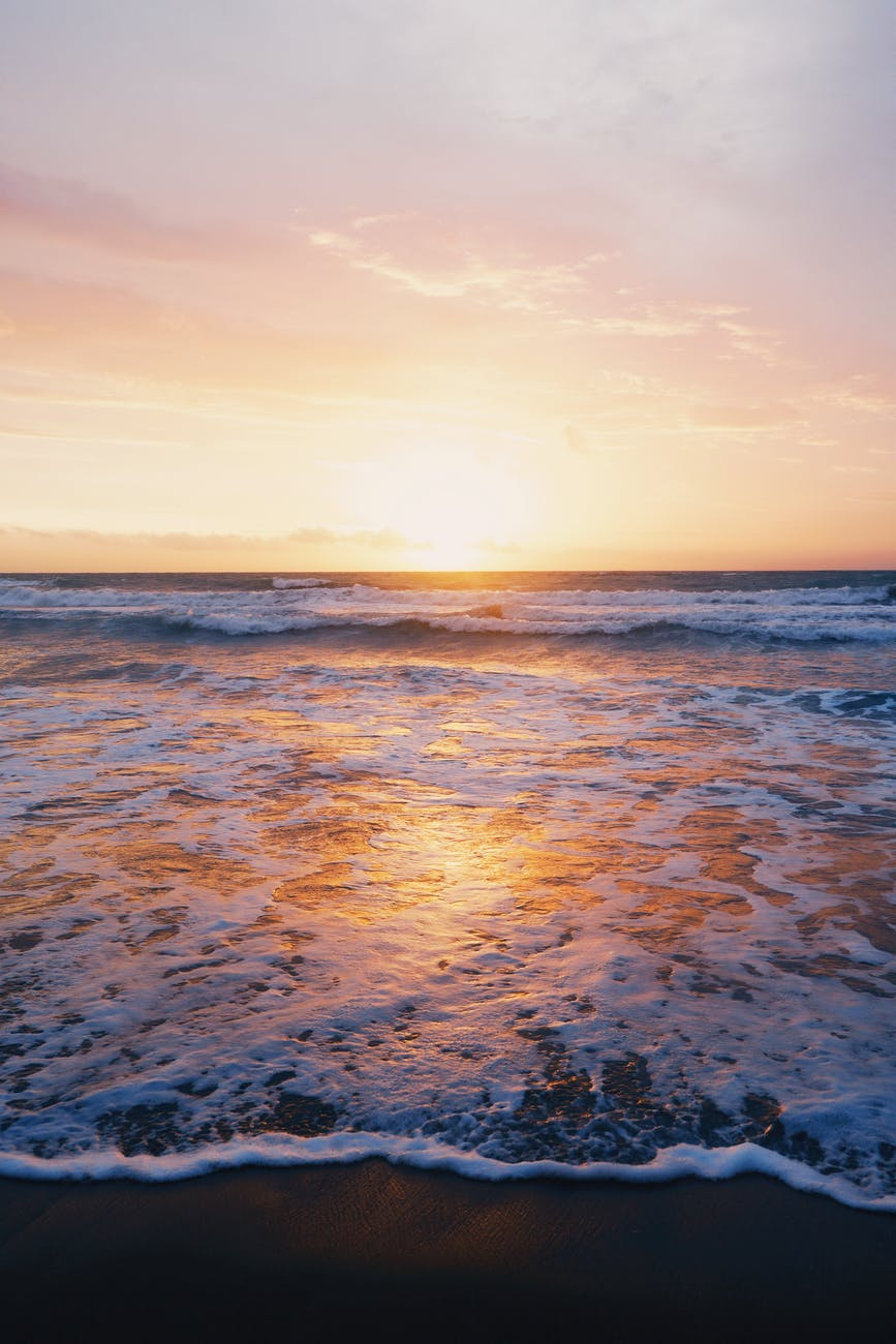 photo of ocean waves near seashore during sunset