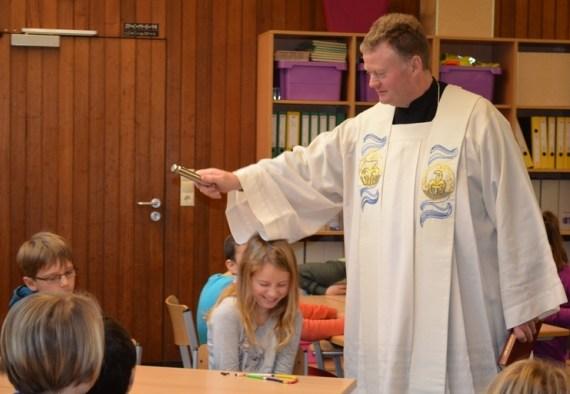 Pastor Wellenbrock segnet die fertigen Rosenkränze der Klasse 4c in der Schule.