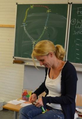 Frau Dudko unterstützt die Kinder bei ihrer Arbeit an den Rosenkränzen.