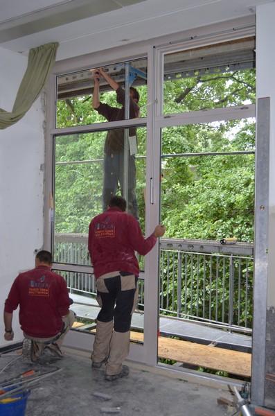 Gemeinsam werden die großen und schweren Elemente der Glasfront sorgfältig eingebaut.
