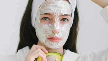 serious woman with cosmetic product on face