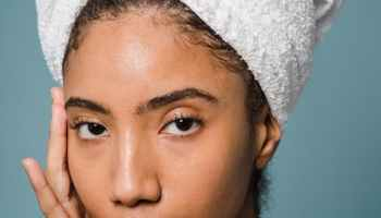 graceful young ethnic woman applying cream on face after shower