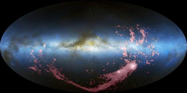 Der Magellansche Strom, eine Schleppe aus Wasserstoffgas, die die Magellanschen Wolken hinter sich her ziehen. Das rot gefärbte Gas wurde im Radiobereich aufgenommen und dem Bild der Milchstraße und der Magellanschen Wolken im sichtbaren Licht überlagert. Bild: NASA, gemeinfrei.