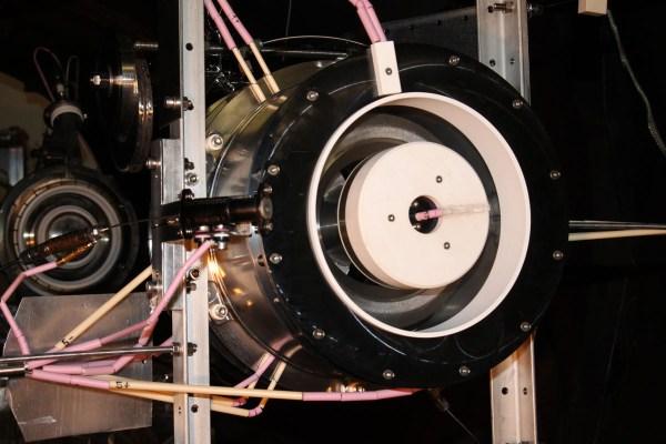RAM_HET in der Testkammer mit Blick auf die Austrittsöffnung. Neben dem weiß verkleideten Magneten sieht man links die kleine röhrenförmige Kathode, aus der die Elektronen in das Plasma injiziert werden. Bild: © ESA, frei für Bildungszwecke.