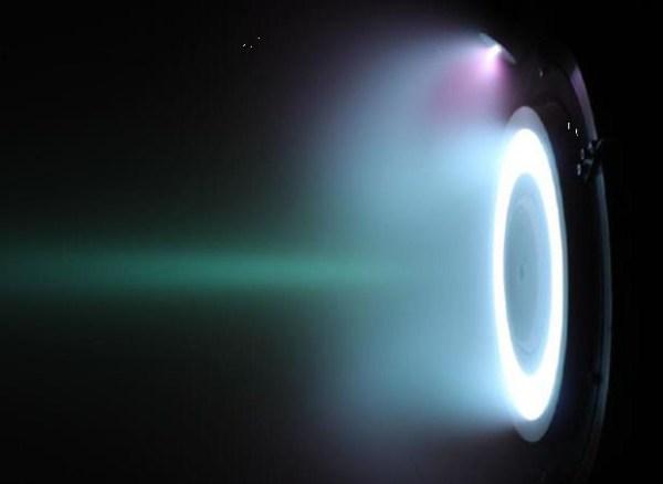 RAM-HET mit Xenon-Gas als Stützmasse. Die Kathodenröhe ist oberhalb erkennbar. Das Xenon-Plasma leuchtet bläulich. Bild: © ESA, frei für Bildungszwecke.