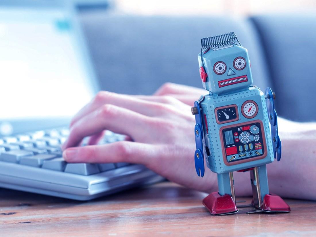 A little robot near a keyboard of a laptop