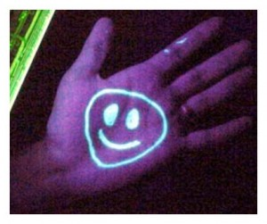 The smiley face on the hand is drawn with a substance containing a phosphor, such as Vasoline (petroleum jelly). Under a black light the phosphors glow.