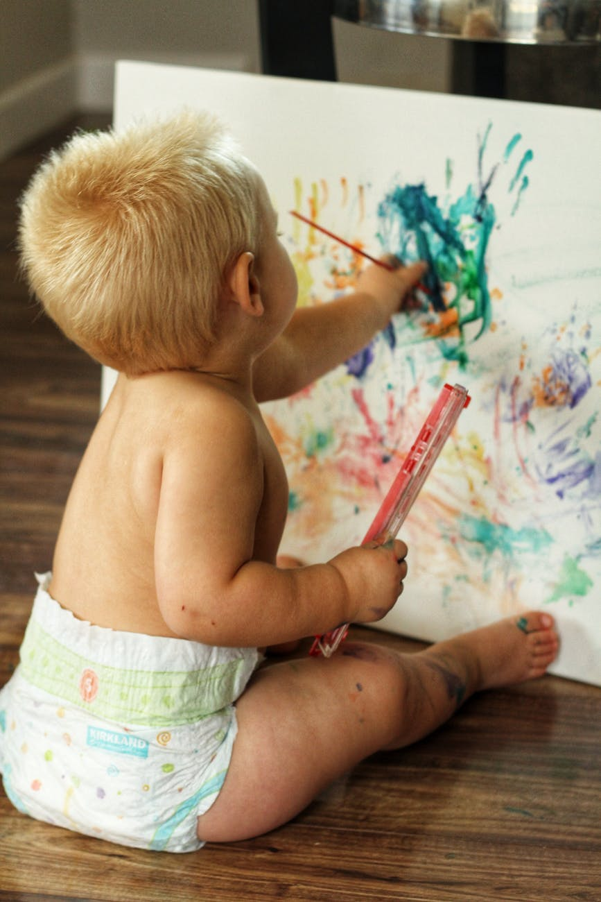 unrecognizable little child painting on paper sheet at home