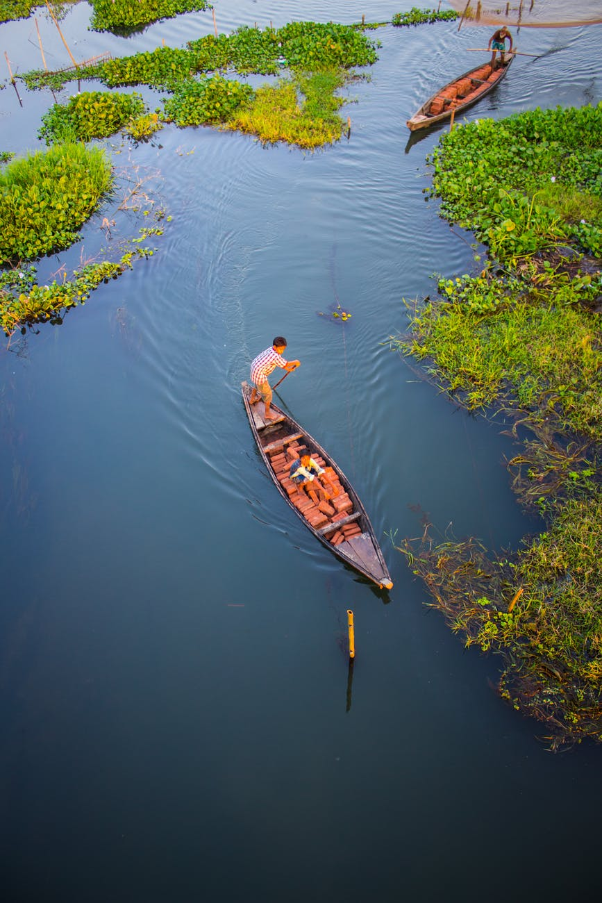 two person riding black wooden boats