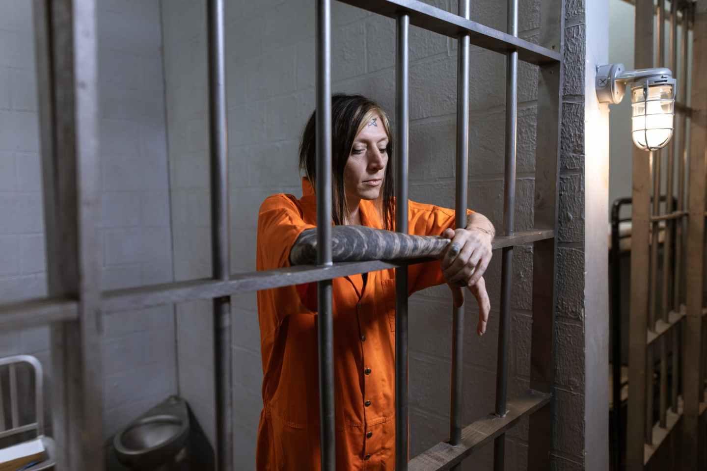 woman in orange long sleeve dress standing beside black metal gate