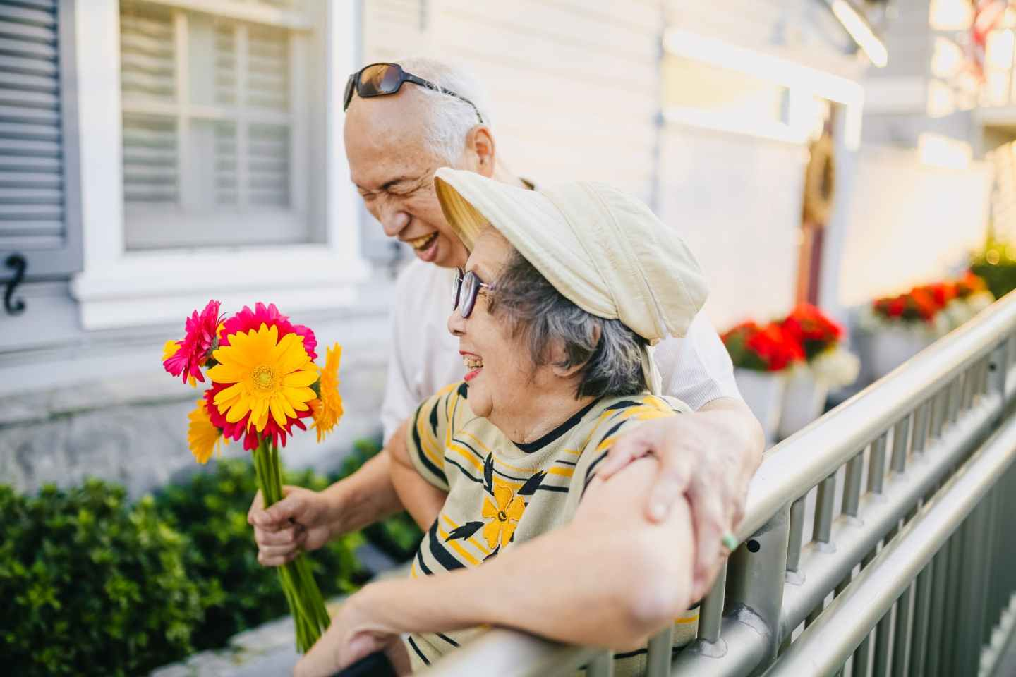 elderly man giving colorful flowers to his wife