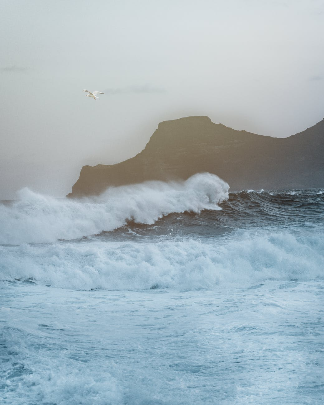 stormy sea waving near rocky cliff