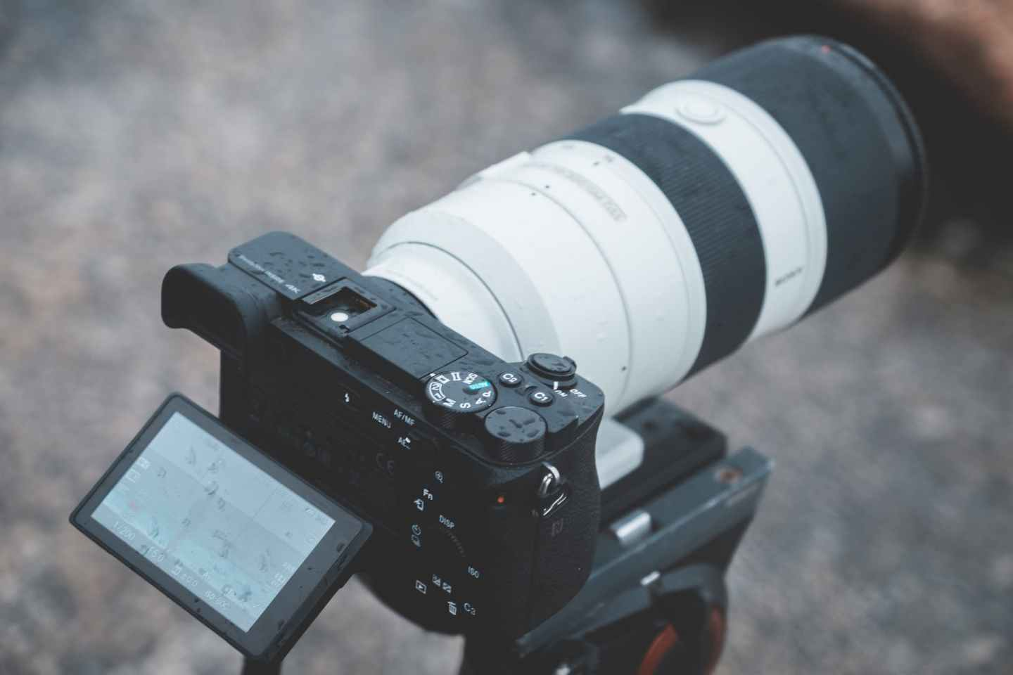 professional photo camera with long focus lens placed on street