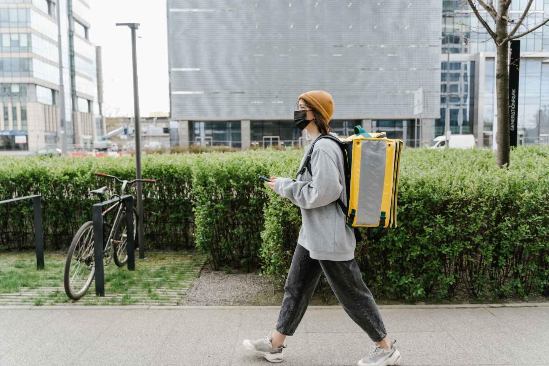 woman carrying a yellow bag walking