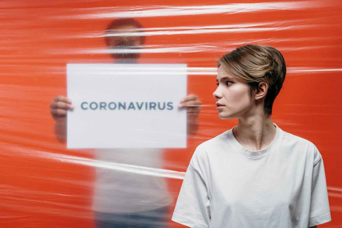 woman in white crew neck t shirt standing beside a man holding a placard of coronavirus
