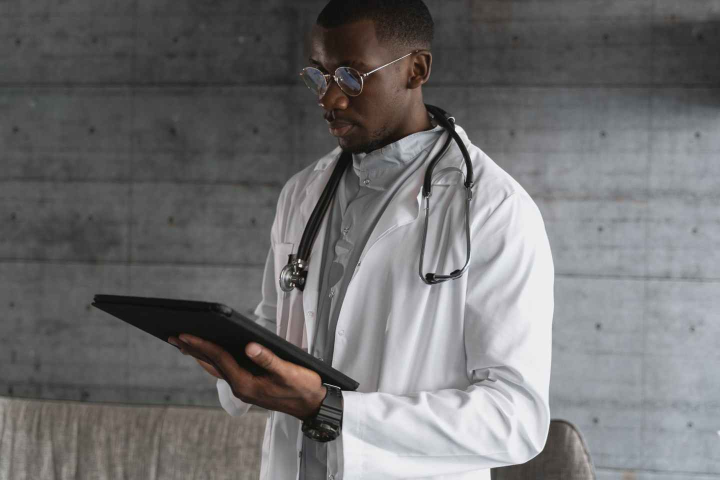 man in white coat holding black tablet computer