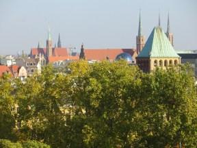 Tu mamy park nad fosą, wieżę zakładów kąpielowych, a w tle sylwetki dominant Ostrowa Tumskiego: kościół Św. Krzyża i katedra pw. św. Jana Chrzciciela.