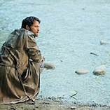 Castiel kneels by the river.