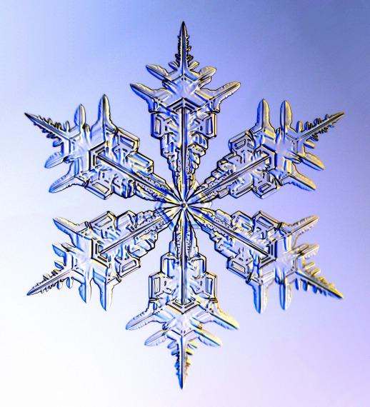 Image description: Clear snowflake against a blue background.