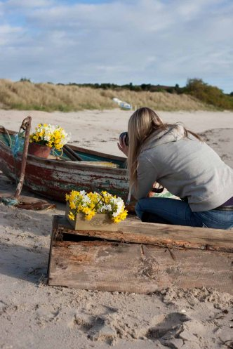 Tamara taking advantage of the sun and winter light to shoot narcissi on the beach in a boat