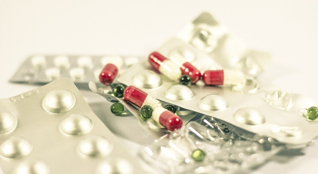 Different types of medication, including silver blister packs, small green liqui-gels, and red and white capsules.