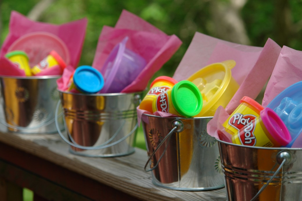 Alternative goody bags: metal reusable pails with brightly colored containers of playdough and kinetic sand.