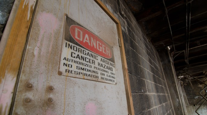 "Dirty metal door with pink paint splatters and a sign that reads ""Danger: Inorganic arsenic cancer hazard authorized personnel only no smoking or eating respirator required""."