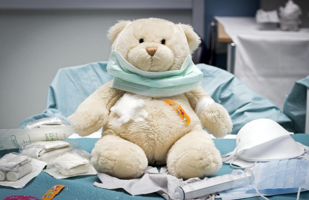 Cream colored teddy bear sitting on a medical exam table with sterile bandages and other medical supplies, with a bandaid on its chest and wearing a paper mask.