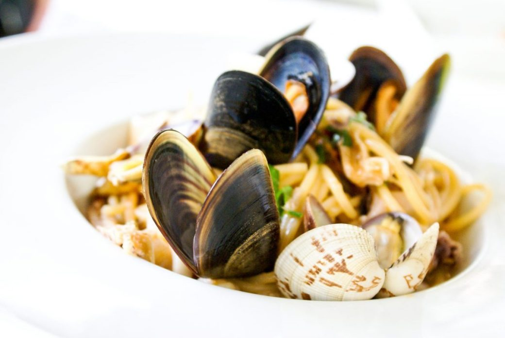 White bowl containing seafood with pasta.