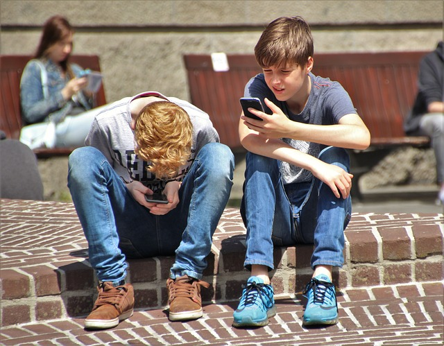 Two teens using mobile phones