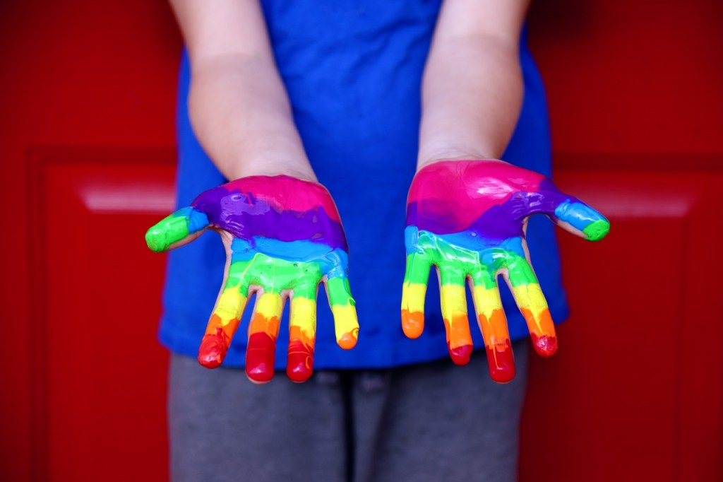 Child hands rainbow paint