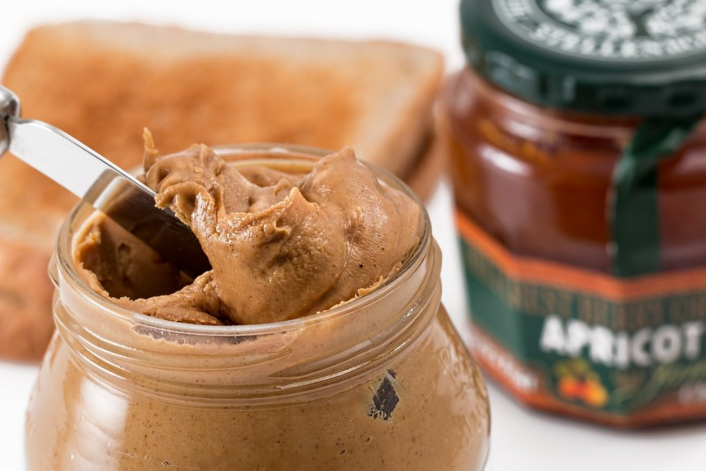 Open jar of peanut butter with butter knife in jar