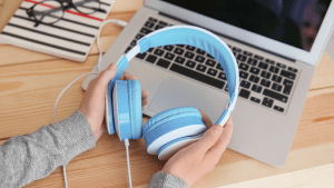A person's hand hold a set a blue headphones over a laptop computer on a desk.