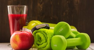 Fitness or diet concept: dumbbells, fresh red smoothie, apple, towel and activity tracker over wooden background. Toned image. Selective focus