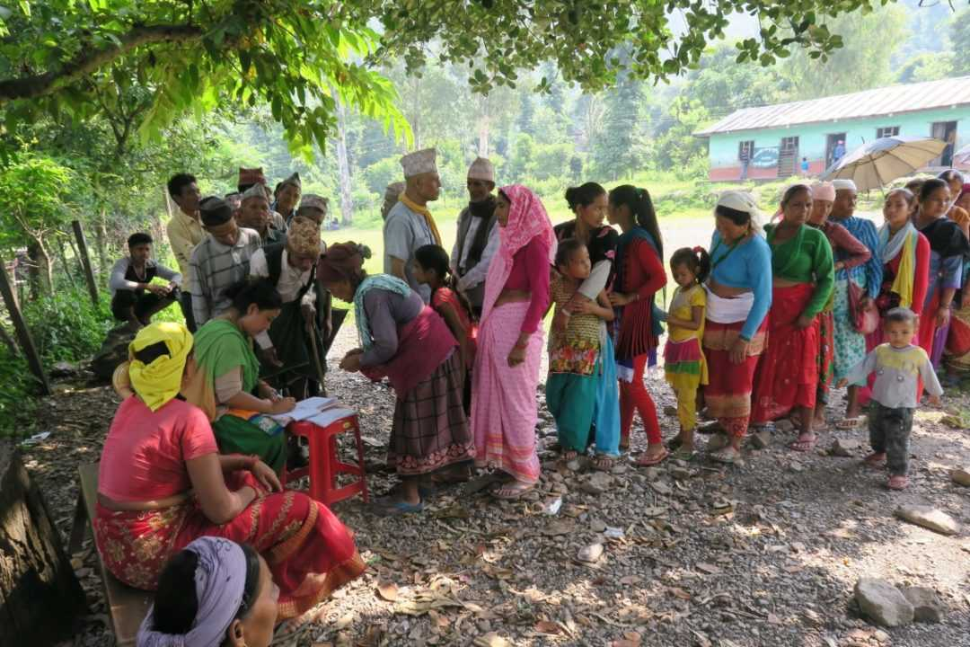 Registering patients under a tree at a mobile health clinic