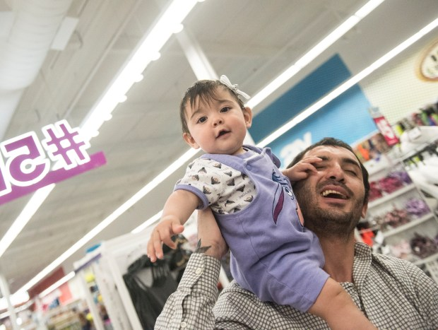 Ciro Brudagljo of Laguna Niguel tours Five Below with 8-month-old daughter Tania, who's less interested in commerce than playing with dad at the Aliso Viejo location. (Photo by Cindy Yamanaka, Orange County Register/SCNG)