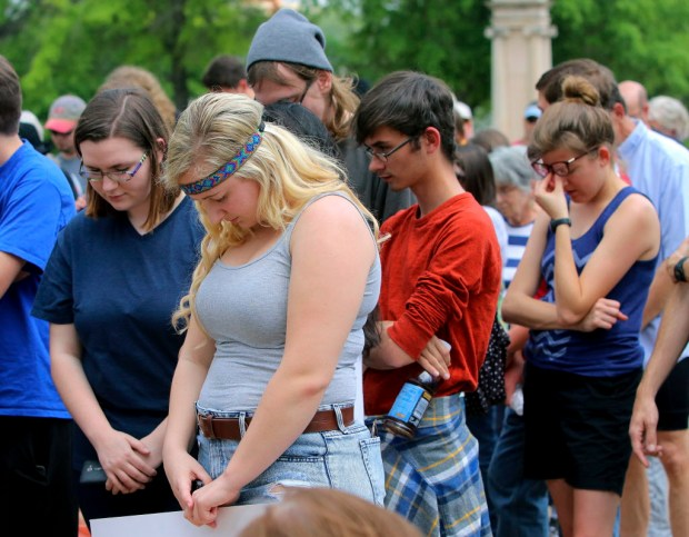 Drew Davis, center with headband, of Ft. Smith, Ark., joins others in a moment of silence during a rally opposing Arkansas' upcoming executions, which are set to begin next week, on the front steps of the Capitol Friday, April 14, 2017, in Little Rock, Ark. (Stephen B. Thornton /The Arkansas Democrat-Gazette via AP)