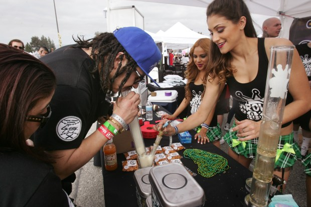 "Alexis ""Goody"" Matias of New York takes a hit from a bong at the Valley OG booth, as Marina Paganessi acts as budtender, at right, during the Cannabis Cup at the Orange Show on Saturday, February, 7, 2015."