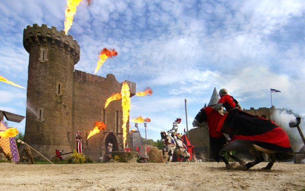 "A knight on a horse charges a castle during a live show experience at Puy de Fou theme park in France. The theme park does many epic live shows in a counter-programming approach to theme park shows and adventures, yet still manages to immerse visitors in the ""olden"" times. (Photo courtesy: Puy de Fou)"