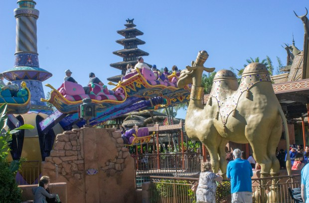 "Riders on board the Magic Carpets of Aladdin dodge the camel's ""spit"" (actually spurts of water) as they fly around Aladdin's lamp in Adventureland at the Magic Kingdom of Walt Disney World. While on board, riders in the front seat control the height of their carpet. (Photo by Mark Eades, Orange County Register/SCNG)"